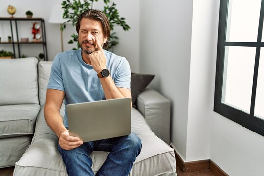 Handsome middle age man using computer laptop on the sofa pointing to the eye watching you gesture, suspicious expression