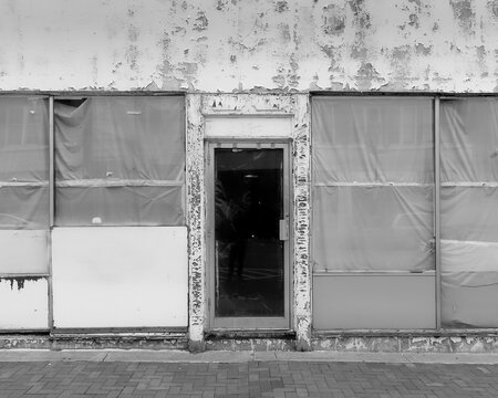 Closed storefront with peeling paint and stucco