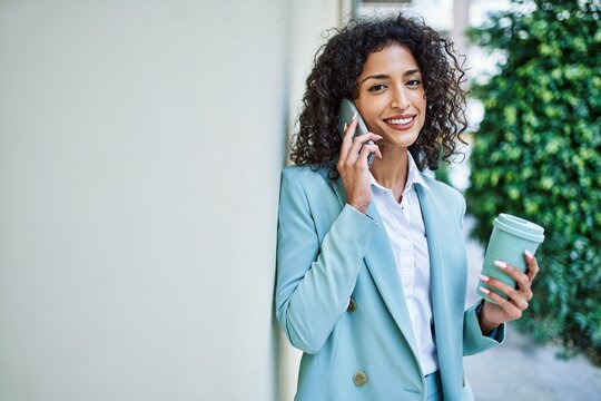 Young hispanic business woman wearing professional look smiling confident at the city speaking on the phone