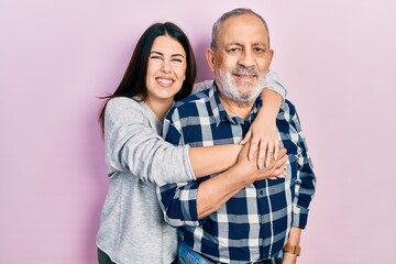 Fototapeta Young brunette woman and senior man standing over pink background. Daughter and father hugging and bonding together as happy family obraz