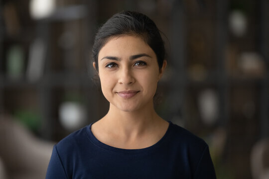 Headshot portrait of happy millennial Indian woman look at camera posing in own house or apartment. Profile picture of smiling young mixed race female renter tenant. Rent, real estate concept.