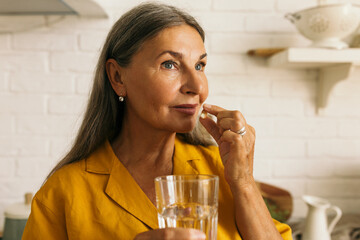 Obraz Cute mature female holding drugs and glass of water in hands. Elderly woman taking medication. Treatment course or vitamins complex idea. Healthy lifestyle and healthcare concept - fototapety do salonu
