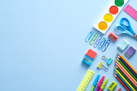 Back to school background with school supplies on blue desk. Flat lay, top view, ovehread.