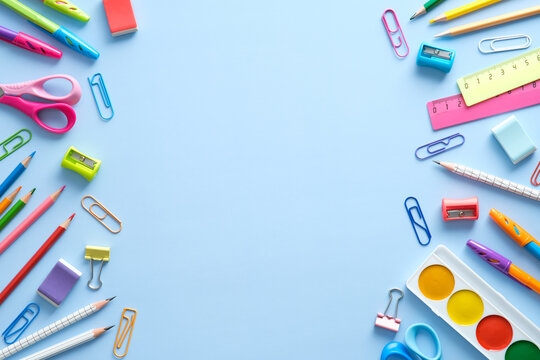 Flat lay colorful school supplies on blue background. Back to school concept. Top view, overhead.