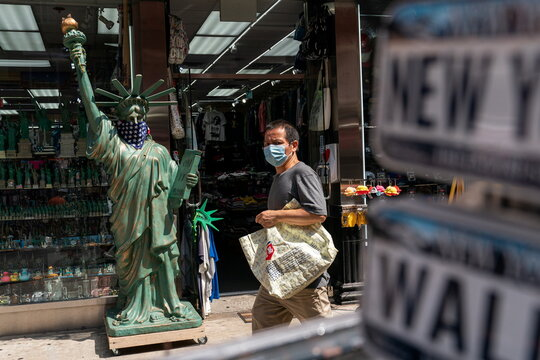 A man wearing a mask walks past a model of Statue of Liberty at a tourist store in New York City