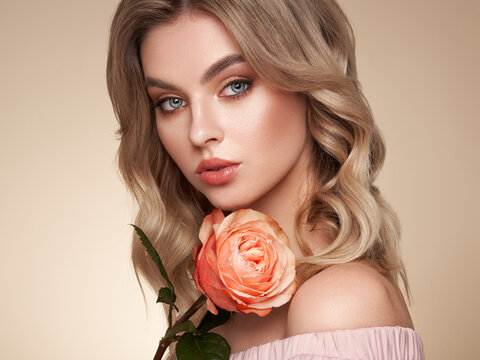 A beautiful young woman with shiny wavy blonde hair. Model with healthy skin, close up portrait. Girl with a rose flower
