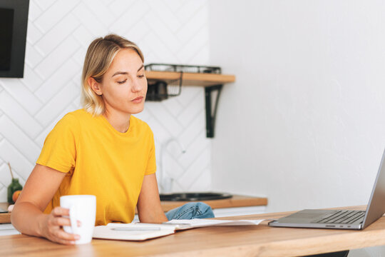 Young blonde woman in yellow t-shirt working at laptop in kitchen at home, girl with cup of the morning coffee with papers