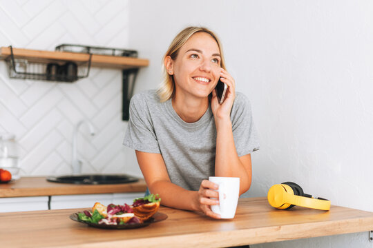 Young smiling blonde woman in yellow t-shirt with cup of tea talking on mobile phone in hands in the kitchen at home