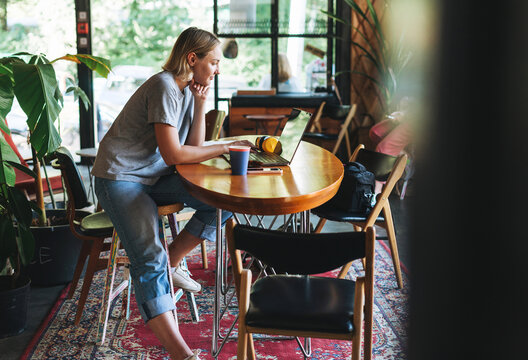 Young smiling blonde woman freelancer in yellow headphones working on laptop on table at cafe