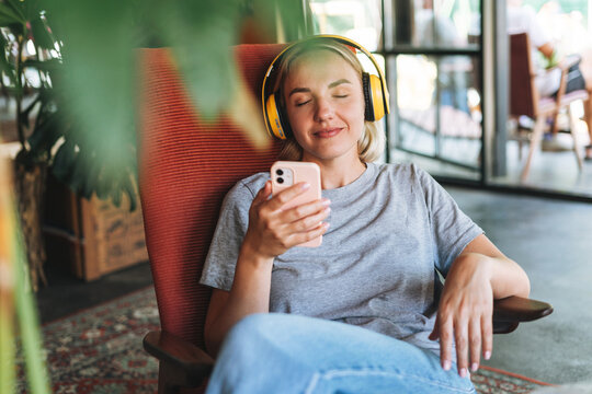 Young smiling blonde woman with close eyes in yellow headphones enjoys music with mobile phone sitting on the chair at cafe