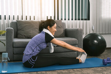 Fototapeta Asian women do stretching exercises after taking yoga classes while at home. obraz