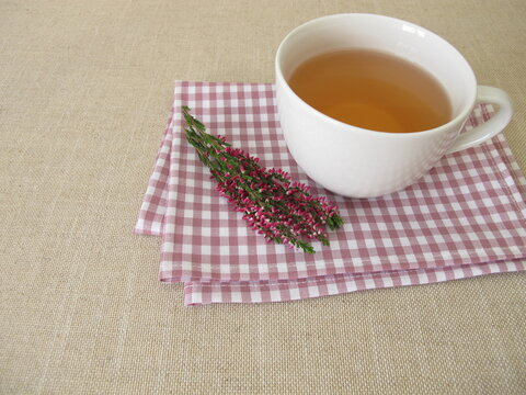A cup of heather tea and flowering shoots from calluna vulgaris