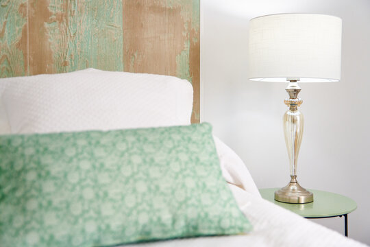 A vertical shot of pillows on the bed in the white lantern background