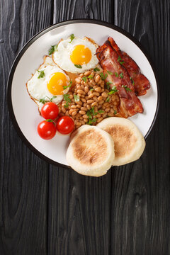 Hot hearty breakfast of fried eggs, beans, bacon, tomatoes and muffins close-up in a plate on the table. vertical top view from above