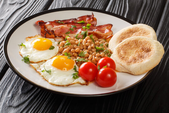 Delicious breakfast or lunch with fried eggs, beans, bacon, tomatoes and English muffins close-up in a plate on the table. horizontal