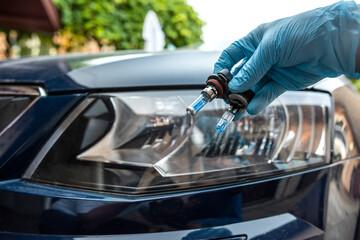 Obraz mechanic hold car halogen light bulb for repair against headlight auto in background - fototapety do salonu