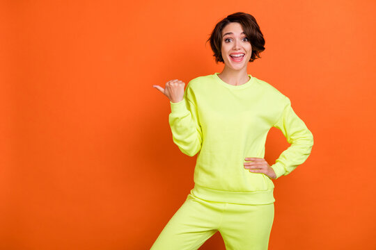 Photo of cheerful young happy positive woman point finger empty space hold hand waist isolated on orange color background