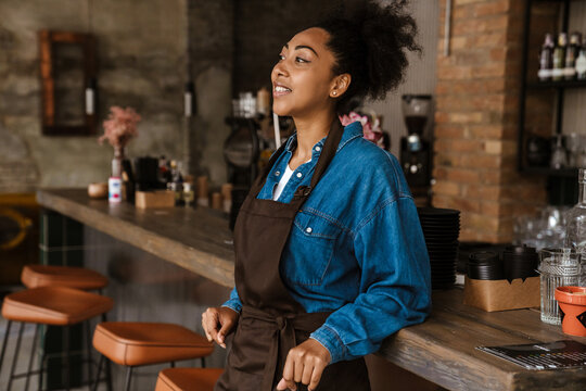 Black waitress wearing apron standing while working in cafe outdoors