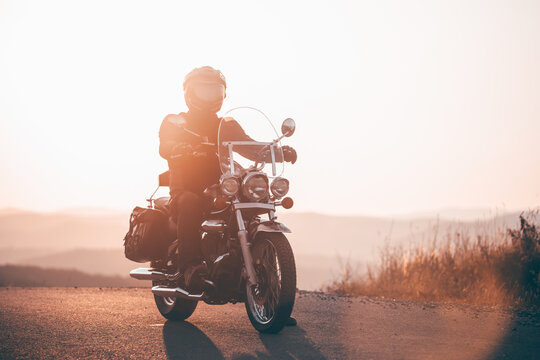 Driver riding motorcycle on an empty road