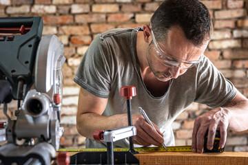 Fototapeta Professional carpenter working with a miter saw. obraz
