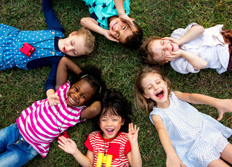 Fototapeta Group of kindergarten kids lying on the grass at park and relax with smiling obraz