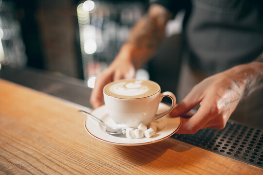 White cup of coffee, latte or cappuchino with marshmallow on wooden bar counter in cafe. Close up