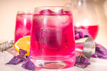 Fototapeta Purple basil organic drink, infused water cocktail with lemon and ice, on a tile background obraz