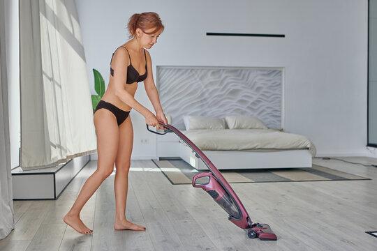 Woman in her 40s is vacuuming floor, dressed in underwear