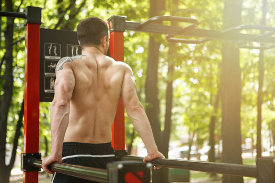 Unrecognizable sportsman working out on calisthenics equipment in the forest