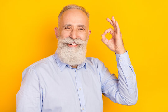 Photo of attractive happy old man smile good mood show okay sign agree isolated on shine yellow color background