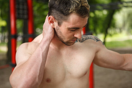Close up of a muscular shirtless man rubbing achine neck after exercising