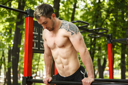 Shirtless male athlete with ripped torso exercising outdoors