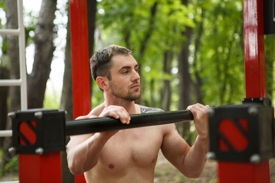 Handsome shirtless athletic man resting after outdoor workout
