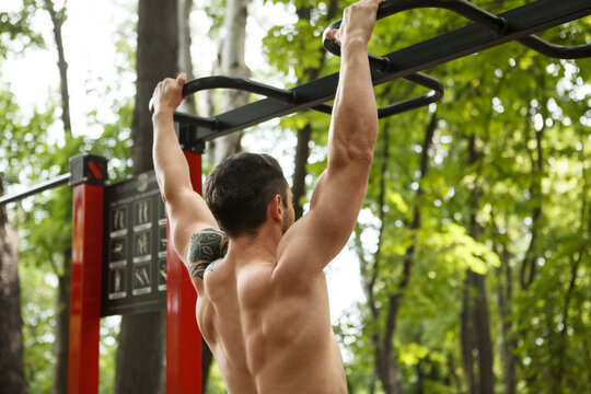 Cropped shot of an athletic muscular man doing pull ups on calisthenics workout playground