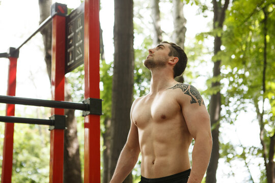 Handsome muscular man standing shirtless outdoors after working out
