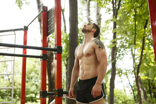 Low angle shot of a shirtless sexy male athlete with perfect muscular body, resting after exercising outdoors