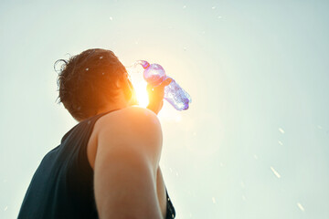 Fototapeta Man pouring water from plastic bottle on his head in hot day obraz