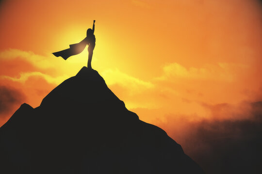 Woman in cape celebrating success on creative backlit mountain and sunset background with mock up place for your advertisement. Leadership and successful concept.