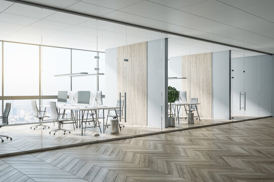 Sunny hall of modern office area with parquet, stylish workspaces, wooden decoration on wall and glass transparent walls and doors