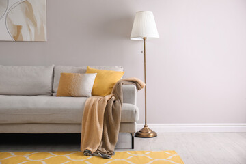 Fototapeta Comfortable sofa with cushions and plaid in stylish living room, space for text. Interior design obraz