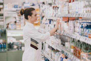 Obraz Woman pharmacist checking medicine in pharmacy - fototapety do salonu