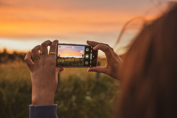 Fototapeta person taking pictures of a field at sunset golden hour obraz