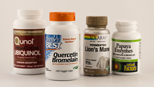 dietary supplements in the jars: ubiquinol, quercetin, bromelain, lion's mane, papaya enzymes. dietary supplements selective focus editorial photo