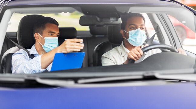 driver courses, health and people concept - young man and driving school instructor in mask with clipboard in car