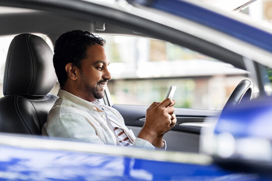 transport, people and technology concept - smiling indian man or driver using smartphone in car