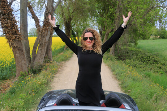 woman with a sports car convertible rural scene