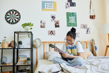 Fototapeta Full length portrait of Asian teenage girl playing ukulele while sitting on bed in cozy room, copy space obraz