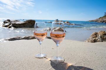 Fototapeta Summer time in Provence, two glasses of cold rose wine on sandy beach near Saint-Tropez, Var department, France obraz