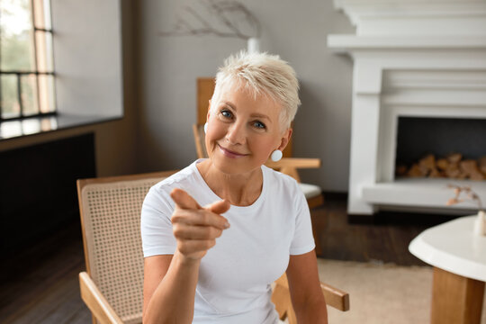 Cheerful mature female sit in living room pointing at you with finger. Ask question are you happy person. Concept of happiness, strong emotion, joy and appreciation of life concept