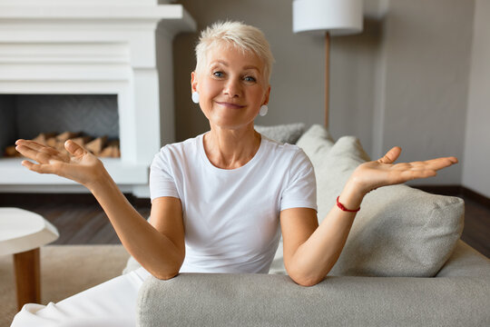 Wise senior female with calm smile on couch throwing up hands in despair. Something went wrong, fail of plans, ruined day. It is what it is, acceptance, go with flow concept